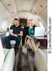 Business Colleagues Discussing On Private Jet - Young...