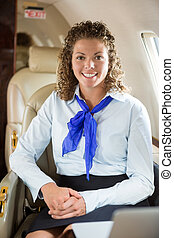 Happy Airhostess Sitting In Private Jet - Portrait of happy...