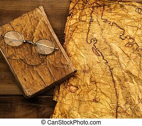 Glasses and book on a vintage paper over wooden background