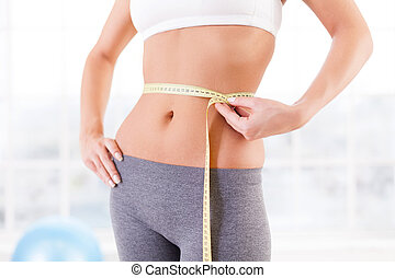 Work out results. Cropped image of young woman in sports clothing measuring her hip and holding hand on hip