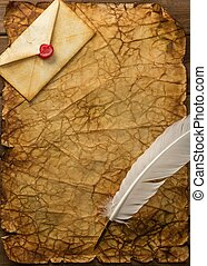 Envelope and quill pen on vintage paper over wooden background