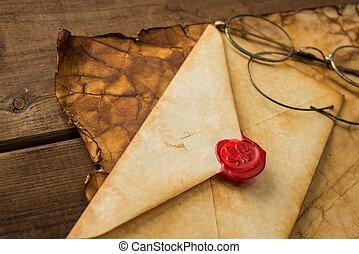 Envelope and glasses on vintage paper over wooden background