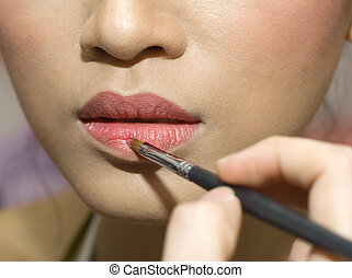 makeup - A young woman applying makeup