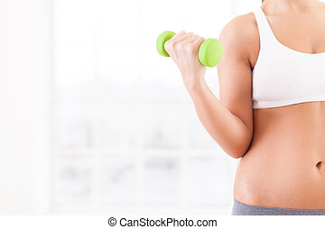Exercising with dumbbells. Cropped image of young woman in sports clothing holding dumbbells