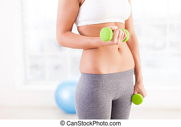 Woman exercising with dumbbells. Cropped image of young woman in sports clothing using dumbbells while exercising