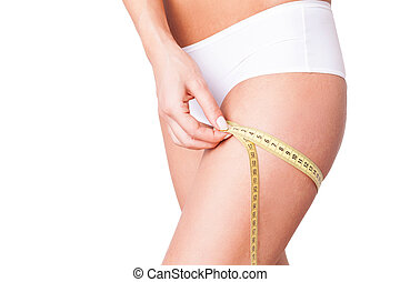 Woman measuring haunch. Cropped image of woman in white...