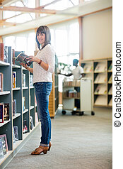 College Student Holding Book In Bookstore - Full length...