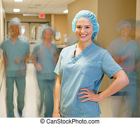 Doctor With Team Walking At Hospital Corridor - Portrait of...