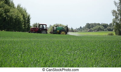 season work fertilizing - green tractor pull a tank with a...