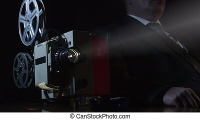 Man watching film on old movie projector - Man dressed in...