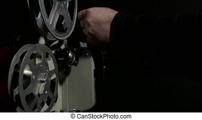 Projectionist operates a movie projector