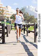 young woman jogging at the beach - beautiful young woman...