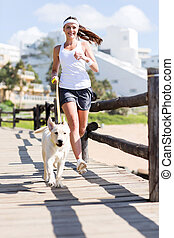woman jogging with her dog - happy woman jogging with her...