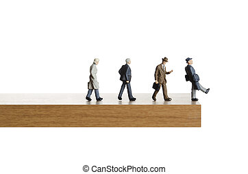 Walking on the edge. - Business figurines walking off a...