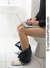 young man in toilet using laptop