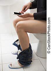young man in toilet using smart phone