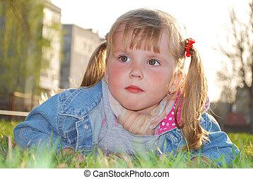 Spring  little girl lying on the grass.