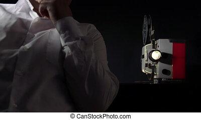 Man watching film on vintage movie projector