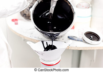 Mechanic preparing black paint for working on a car in...