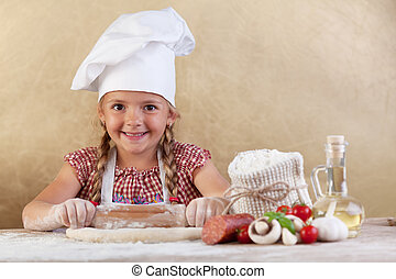 Happy chef little girl stretching the dough - with food...