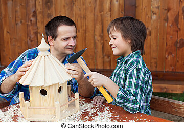 Father and son building a bird house together - Smiling...