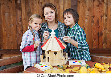Family in autumn time preparing a bird house