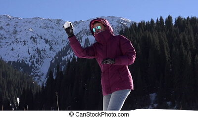Game of Snowballs - Young woman throwing snowballs on a...