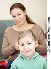 Mother plaiting the hair of her daughter sitting in domestic...