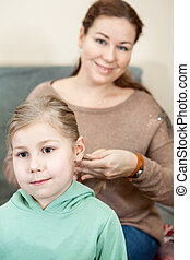 Mother raiding the hair of her child sitting in domestic room