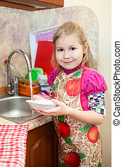 Little girl with a clean plate at the sink