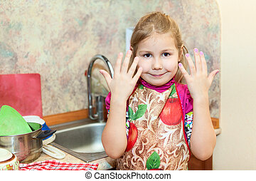 Little girl shows hands after washing dishes