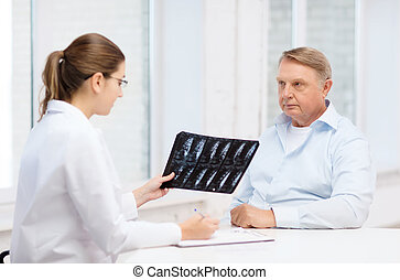 female doctor with old man looking at x-ray - healthcare,...
