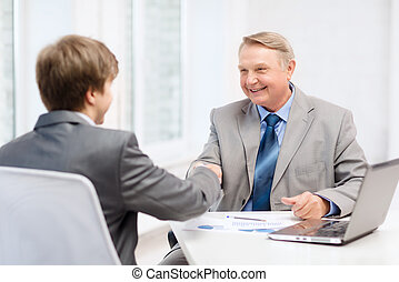 older man and young man shaking hands in office - business,...