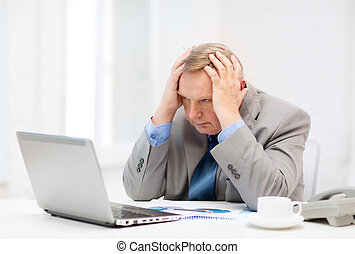 upset older businessman with laptop and telephone -...
