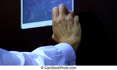 Touch screen on wall - Hand is operating a computer or tv...