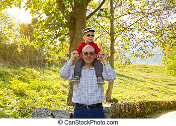 Grandfather holding grandchild on his shoulders - Happiness...