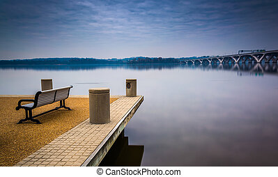 Bench along the Potomac River, in Alexandria, Virginia. -...