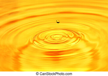 abstract background. A drop of water falls in gold