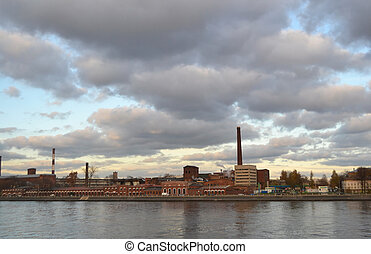 Old factory on river bank at evening, St.Petersburg, Russia.