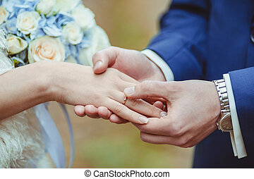 Wedding ceremony - Grooms hand putting a wedding ring on the...