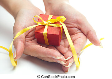 red gift box with a yellow ribbon in the hands of women