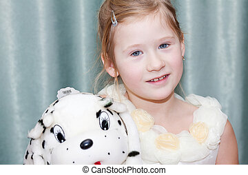 portrait of a beautiful little girl with a toy dog