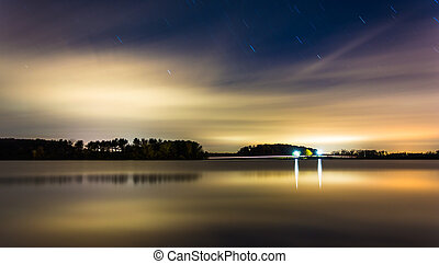 Clouds and stars moving over Long Arm Reservoir at night,...