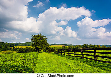 Clouds over fence and farm fields in rural York County, Pennsylvania.