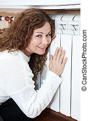 Smiling woman leaning his hand and cheeks to central heating...