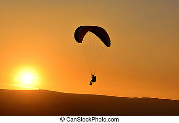 paraglider at sunset - paraglider soar in the air amid...