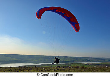 Paraglider taking off from a mountain - paraglider soar in...