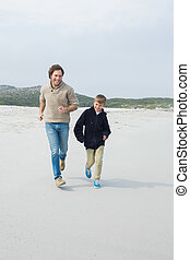 Young man and son jogging at beach - Full length of a young...