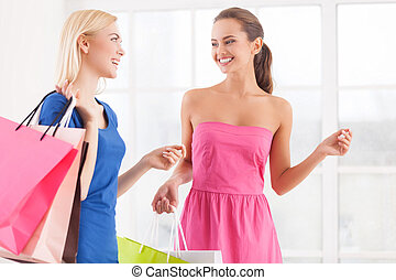 Enjoying shopping. Two cheerful young women in dresses walking together and holding shopping bags