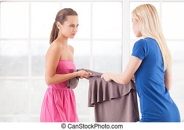 This dress is mine! Two angry young women holding one dress...